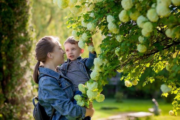 Счастливая молодая мать играет и веселится со своим маленьким сыном в теплый весенний или летний день в парке