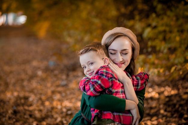 幸せな若い母親は彼女の幼い息子と遊んで楽しんでいます
