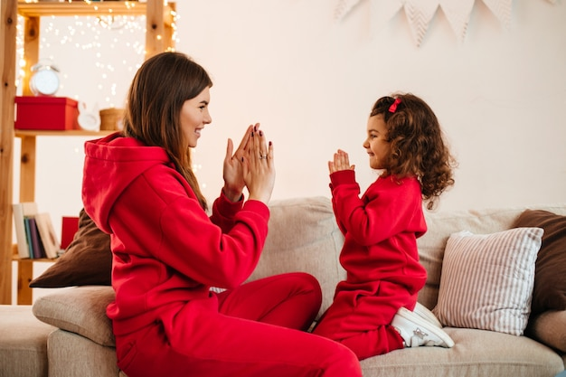Happy young mother playing with daughter on sofa. indoor shot of charming mom and preteen kid in red attire.
