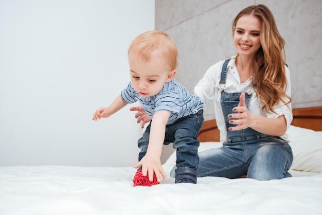 Счастливая молодая мать играет со своим маленьким сыном на кровати у себя дома