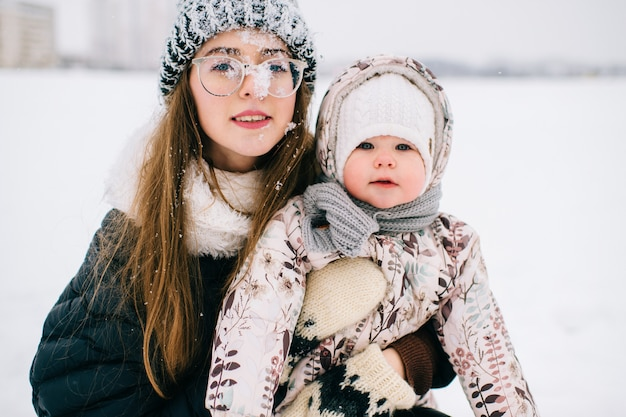 Happy young mother playing with her lovely baby in winter snowy field.