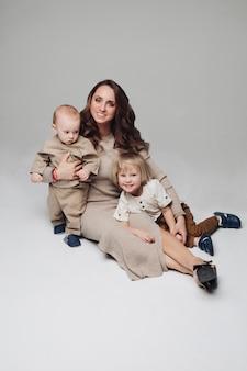 그녀의 아이들과 함께 카메라에 포즈 행복 젊은 어머니