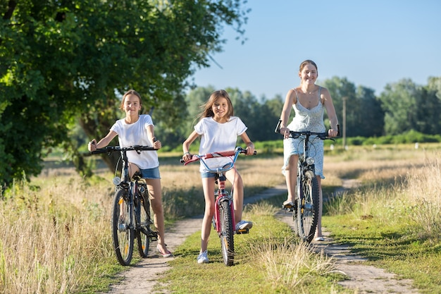Happy young mother riding on bicycles with two daughters
