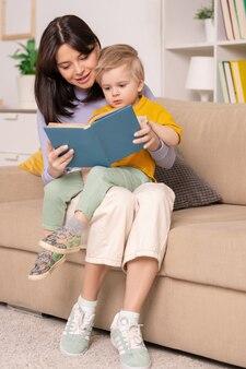 Счастливая молодая мать сидит с маленьким сыном на коленях на диване и читает ему детскую книгу с картинками