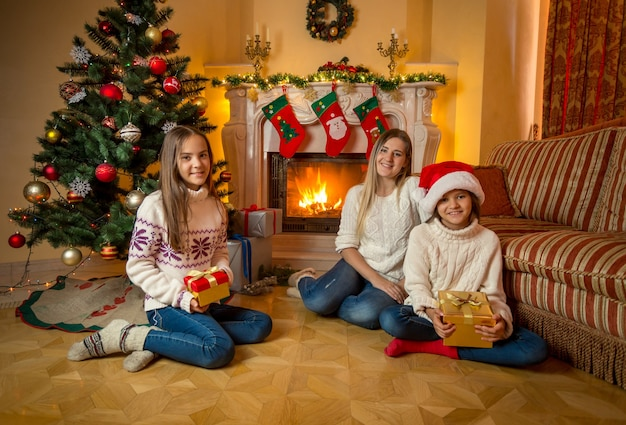 Happy young mother sitting with two daughters on floor next to burning fireplace. decorated christmas tree on background