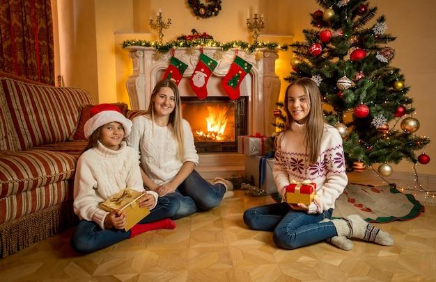 燃える暖炉の隣の床に2人の娘と一緒に座っている幸せな若い母親