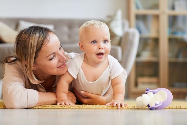 그녀의 작은 아기 아들, 가로 샷과 함께 카펫에 누워 집에서 시간을 보내는 행복 한 젊은 어머니
