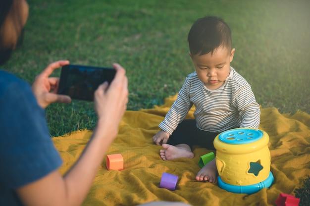 幸せな若い母親は、スマートフォンや携帯電話を使用して、思い出のために息子や子供に写真を撮ります。家族のコンセプト。