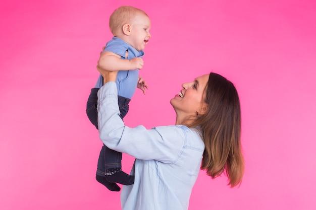 Счастливая молодая мать с младенцем на розовой стене