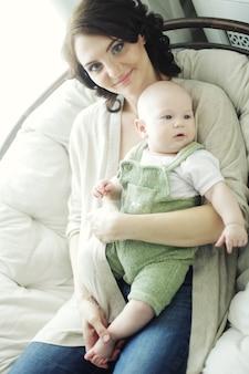 Счастливая молодая мать с ребенком дома