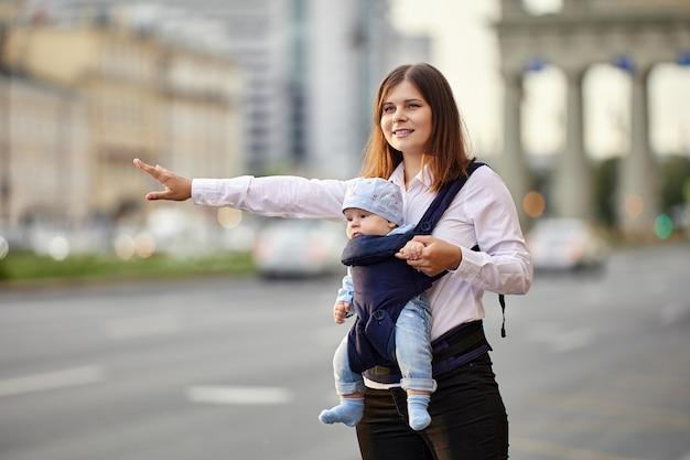 Счастливая молодая мать с ребенком в слинге останавливает такси