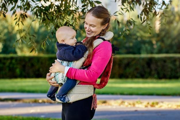 Счастливая молодая мать с ребенком в слинге на открытом воздухе