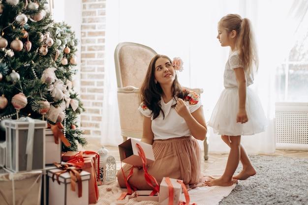 Счастливая молодая мама с цветком в волосах и ее маленькая дочка в красивом платье сидят у новогодней елки и открывают новогодние подарки в светлой уютной комнате.