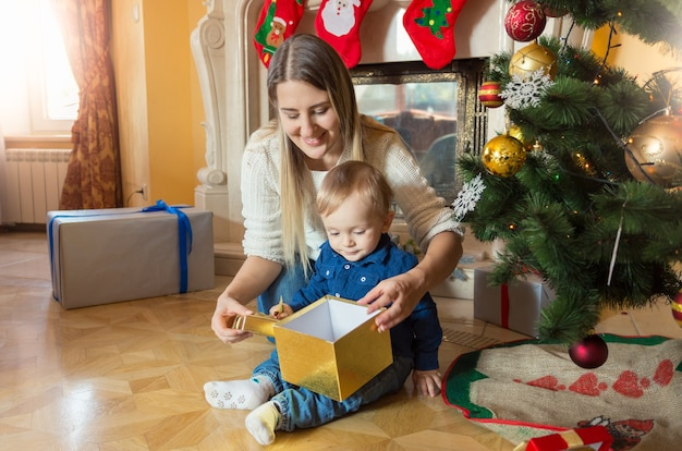아기 아들이 크리스마스 트리에 앉아 선물 상자 안을 들여다보는 행복한 젊은 어머니