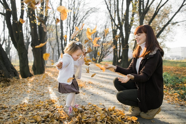 단풍 가지고 노는 그녀의 작은 딸과 함께 행복 한 젊은 어머니