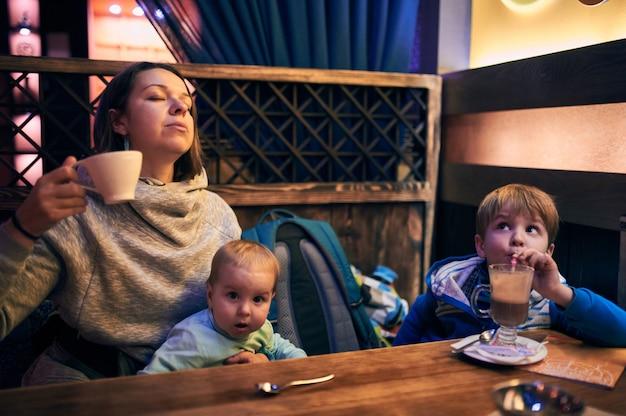 그녀의 두 아이가 앉아 마시는 차와 함께 행복 한 젊은 어머니