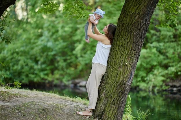 小さな男の子と幸せな若い母親は、散歩中に屋外で遊ぶ