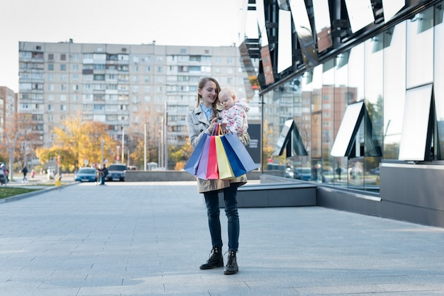 Happy young mother with little daughter on the arms and shopping bags in hand. shopping day. mall on wall