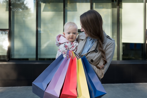 Happy young mother with little daughter on the arms and shopping bags in hand.