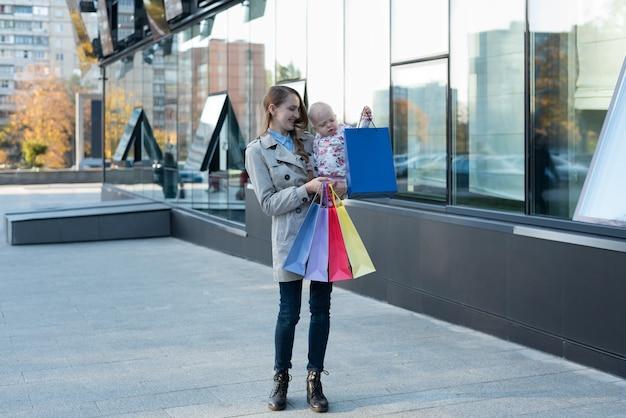 Счастливая молодая мать с маленькой дочерью на руках и хозяйственных сумках в руке. день покупок. торговый центр на поверхности