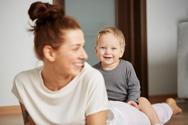 自宅で幼い息子を持つ幸せな若い母親