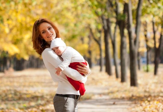 秋の公園を歩いている手に眠っている子供と幸せな若い母親