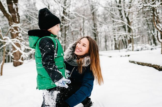 息子と一緒に幸せな若い母親は、ウィンターパークで歩いて遊んでいます。閉じる。屋外で雪の中で走って落ちる肖像画の幸せな家族。