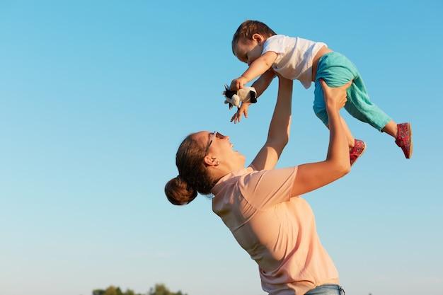 Счастливая молодая мать с малышом в руках, проводя время изолированно над стеной голубого неба, дама с пучком волос проводит время со своим маленьким ребенком в полете.