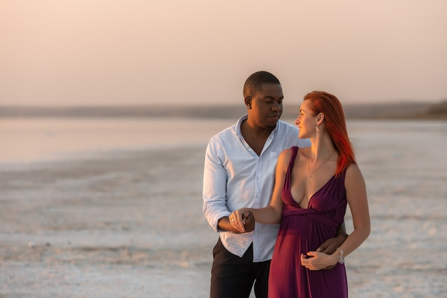 幸せな若い多民族のカップルが抱き締めて、屋外で楽しんでいます。ビーチで一日を楽しんでいる愛するカップル