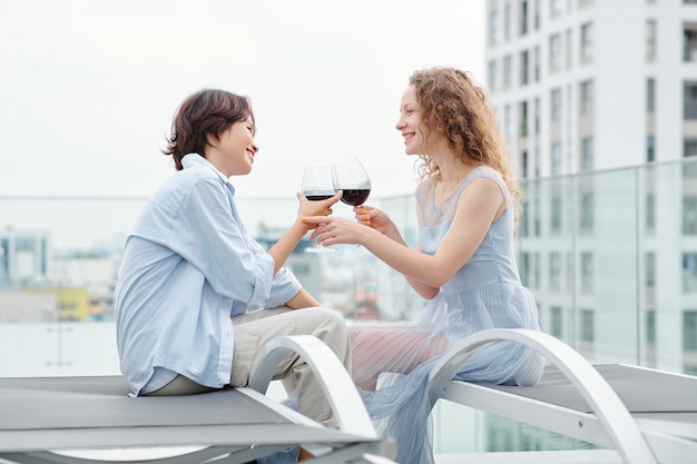 Happy young multi-ethnic lesbian couple drinking wine when having romantic date on rooftop
