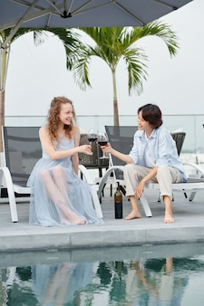 Happy young multi-ethnic lesbian couple sitting on chaise-lounges by swimming pool, talking and drinking wine