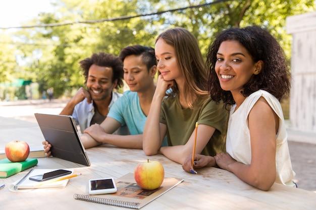 태블릿을 사용하여 야외에서 행복 한 젊은 다민족 친구 학생
