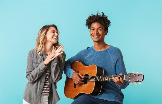 함께 행복 한 젊은 multiethninc 커플, 파란색 벽 위에 절연 기타를 연주