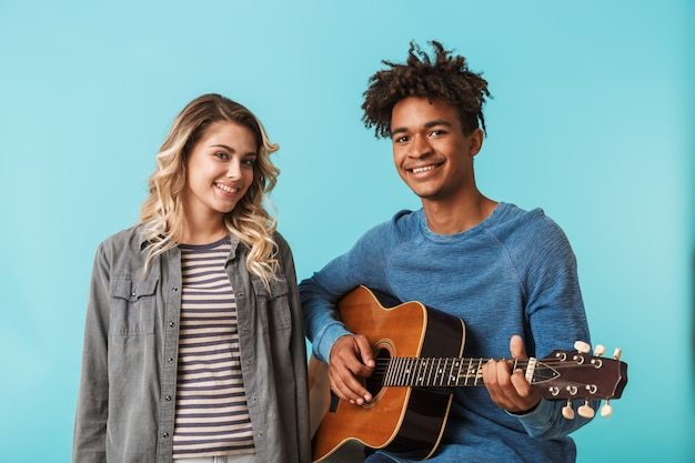 Happy young multiethninc couple together, playing a guitar isolated over blue wall