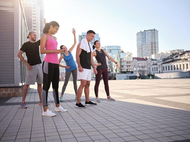 街の広場でウォーミングアップ幸せな若い多民族アスリート