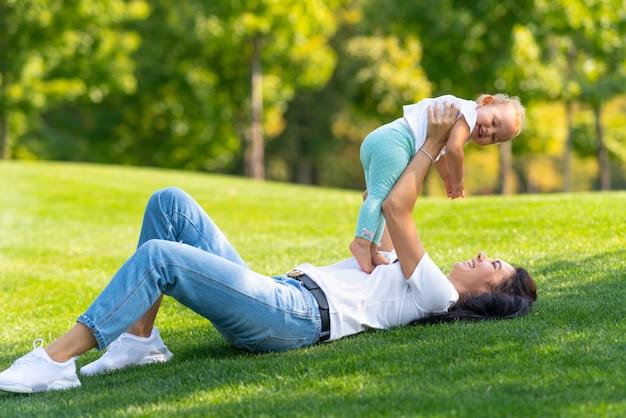 Счастливая молодая мама играет со своей маленькой дочерью, держа ее в воздухе, пока они наслаждаются жарким летним днем на открытом воздухе в тени дерева