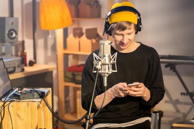 그의 차고에 앉아있는 동안 스마트 폰에서 온라인 기록을 스크롤하는 헤드폰과 casualwear의 행복한 젊은 음악가