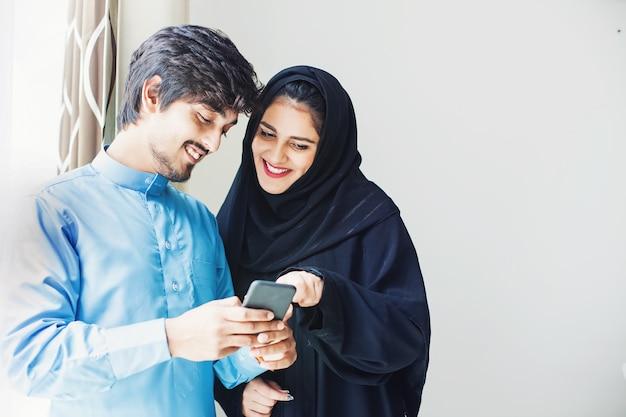 휴대 전화에서 앱을 사용하는 행복한 젊은 이슬람 부부