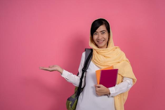 ピンクの背景に笑みを浮かべて幸せな若いイスラム教徒の学生