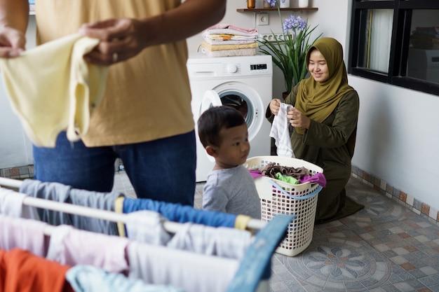 幸せな若いイスラム教徒の女性と彼女の夫は家で一緒に洗濯をしています