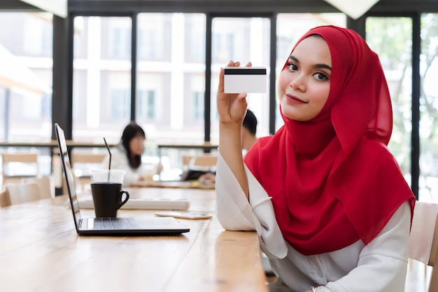 Happy young muslim woman red hijab hand showing credit card mockup in cafe.