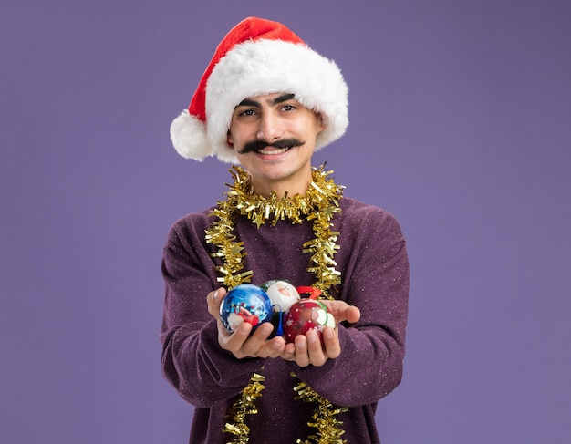 Happy young mustachioed man wearing christmas santa hat with tinsel around his neck holding christmas balls happy and cheerful smiling standing over purple wall
