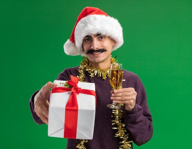 緑の背景の上に立っている顔に笑顔でカメラを見てシャンパンとクリスマスプレゼントのガラスを保持している彼の首に見掛け倒しのクリスマスサンタ帽子をかぶって幸せな若い口ひげを生やした男