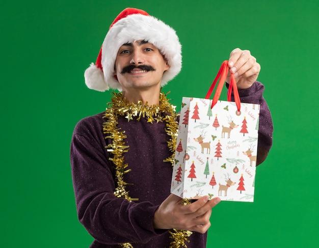 幸せな若い口ひげを生やした男は彼の首に見掛け倒しのクリスマスサンタの帽子をかぶって、緑の背景の上に立って自信を持って笑顔のカメラを見てクリスマスプレゼントと紙袋を保持しています