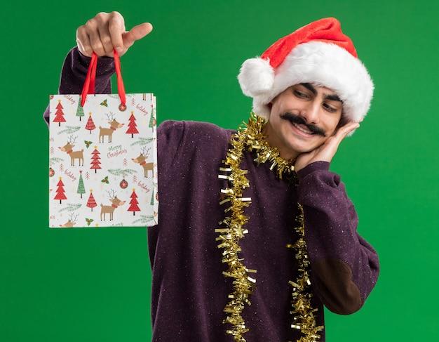 首に見掛け倒しのクリスマスサンタの帽子をかぶって幸せな若い口ひげを生やした男は、緑の背景の上に立っている顔に笑顔でそれを見てクリスマスプレゼントと紙袋を保持しています
