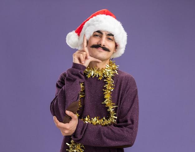 보라색 벽 위에 서있는 손가락 측정 기호로 작은 크기 제스처를 만드는 그의 목 주위에 반짝이와 크리스마스 산타 모자를 쓰고 행복 한 젊은 mustachioed 남자