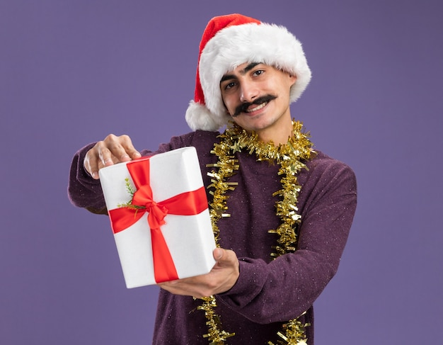 Happy young mustachioed man wearing christmas santa hat with tinsel around his neck showing christmas present   with smile on face standing over purple wall