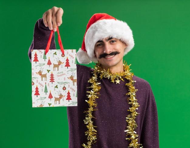 首に見掛け倒しのクリスマスサンタの帽子をかぶって幸せな若い口ひげを生やした男は、緑の背景の上に立っている顔に笑顔でカメラを見てクリスマスプレゼントと紙袋を示しています