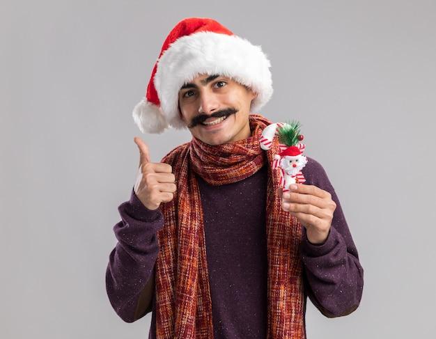 Счастливый молодой усатый мужчина в рождественской шляпе санта-клауса с теплым шарфом на шее, держащий рождественскую конфету, глядя в камеру, улыбаясь, показывает палец вверх, стоя на белом фоне