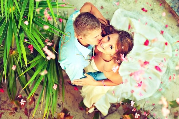 떨어지고 흩어져있는 꽃잎으로 둘러싸인 행복한 젊은 신혼 부부 잘 생긴 신랑은 뺨 아름다운 신부를 포옹하고 키스하고 있습니다. 행복의 목가적 인 순간